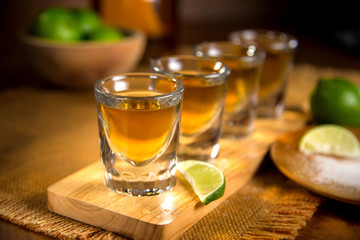 Close up of agave traditional Tequila shots flight with cut limes and salt