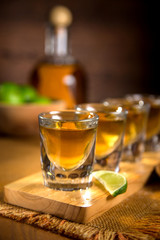 Vertical Close up of Tequila shots grouped together with a bottle and cut limes on a wooden surface