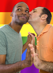 same-sex homosexual couple with a rainbow gay pride flag in the background