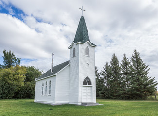 horizontal image of a beautiful quaint little country church sitting on a green lawn surrounded by spruce trees under a white puffy cloud filled sky in the summer time.