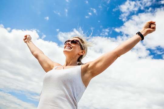 Carefree woman raising her hands in the air