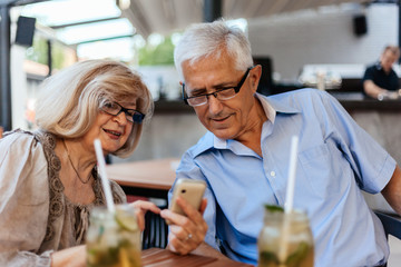 Mature Couple In Cafe Using Technology