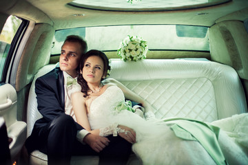 wedding. Bride and groom kissing in limousine on wedding-day.