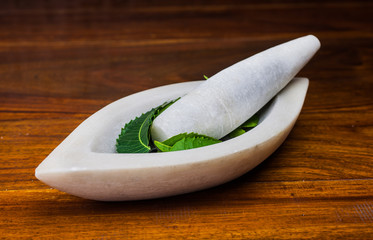 A marble pestle and mortar with neem leaves on a wooden surface.