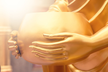 Golden Monk's alms bowl in hand of statue