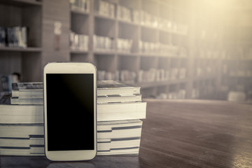 smart phone,cellphone with stack of book on blur bookshelf backg