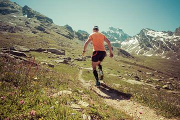 Man running on a single track  in the Alps mountains