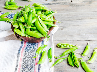 young green peas in the pod, earthenware dish, rustic background