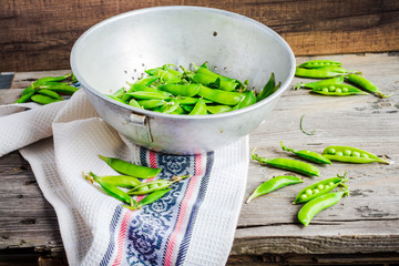 raw green peas in pods young, a metal colander, rustic