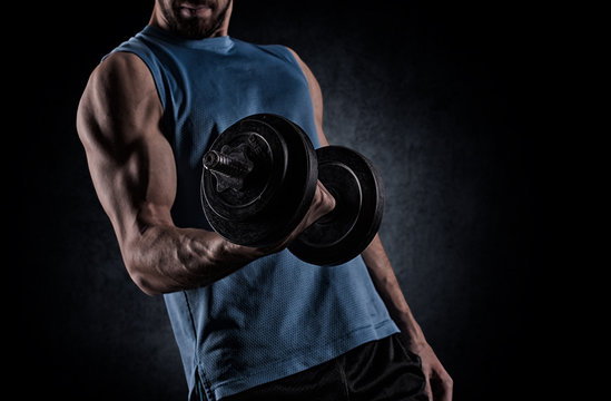 young man with dumbbell flexing muscles over gray background