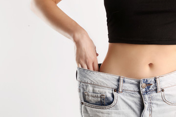 Studio shot of a young caucasian fit female wearing big jeans after diet