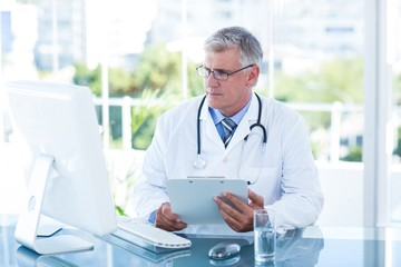 Serious doctor working on computer at his desk