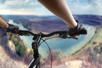 Hands in gloves holding handlebar of a bicycle. Mountain Bike cyclist riding single track. Healthy lifestyle active athlete doing sport