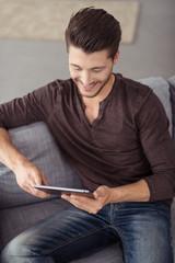 mann sitzt auf dem sofa und schaut auf tablet-pc