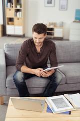 junger mann sitzt auf dem sofa und schaut auf laptop