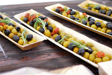 black and green olives, herbs, sun-dried tomatoes in an oblong d