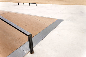 Jump box with rail in an empty skate park.