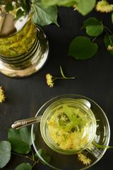 Linden tea in glass cup on dark wooden background