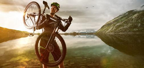 Mountainbiker carries his bike