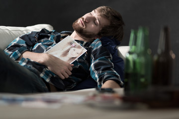 Drunk man lying on couch