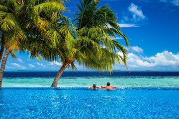 couple relaxing in infinity pool under coco palms in front of the ocean