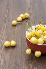 Fresh yellow cherry in a red bowl on a wooden background, selective focus