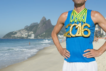 First place athlete wearing 2016 gold medals standing outdoors on Ipanema Beach Rio de Janeiro Brazil