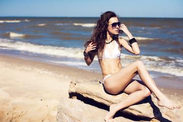 Young, beautiful, slim and sexy woman in bikini on the beach. Tr