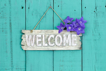 Welcome sign with flowers hanging on teal blue background