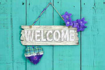 Welcome sign with flowers and heart hanging on teal blue background