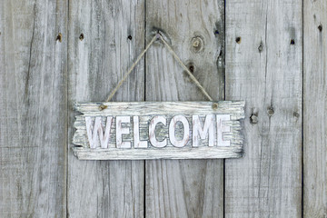 Rustic welcome sign hanging on wood background