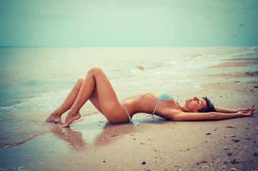Beautiful young woman laying in the sea coast - with toning