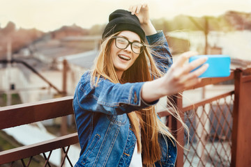 Young sexy blonde hipster woman posing for selfie and laughing. Wearing jeans jacket, hipster black hat and glasses. Lifestyle portrait bright with sun shine.