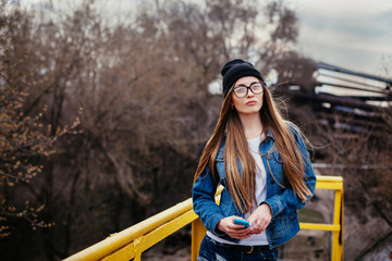 Outdoor fashion lifestyle portrait of pretty young girl, wearing in hipster swag grunge style urban background.