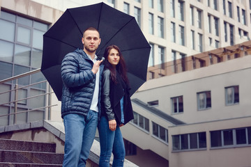 Beautiful young couple in love on a date outdoors on modern urban background. Bearded handsome man and brunette pretty woman in casual dress with umbrella. Rainy weather.