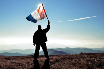 successfull silhouette man winner waving French flag on top of the mountain peak