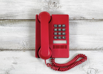 Vintage red phone on rustic white wooden boards