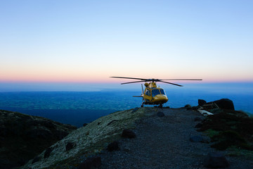 Helicopter on mountain peak at sunset