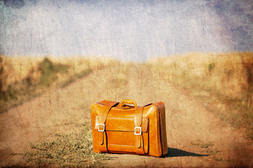 Old suitcase at country side road.