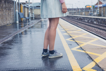 Legs of young woman standing on platform