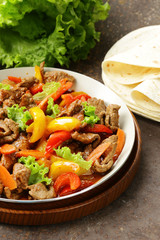 Beef Fajitas with colorful bell peppers in pan on a wooden table