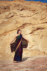 Beautiful girl with indian sari against sand background