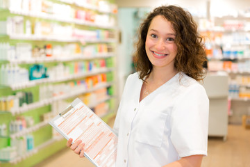 Attractive pharmacist taking notes at work