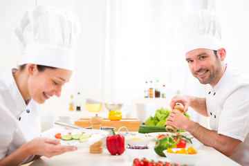 Young attractive professional chef cooking in his kitchen