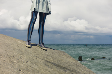Legs of young woman standing by coast