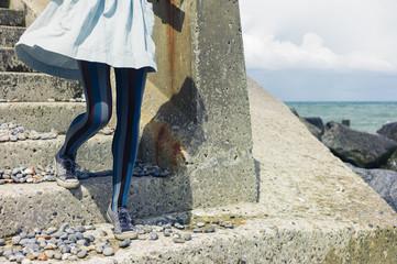 Legs of woman in dress standing on coast