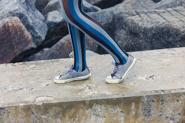 Legs of woman standing on concrete structure by sea