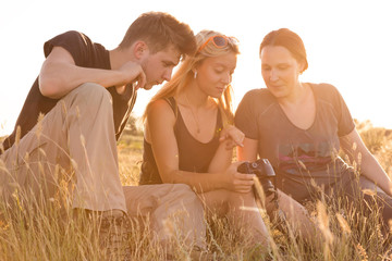 Girl displaying images on her camera to brother and mother. Family of three people sitting on grassy lawn watching on display of photo camera back light sun sunset sun on background