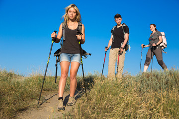 Hiking family. Daughter son and mother walks ground path at wild green yellow grassy hill carrying backpacks and holding trekking gear blue sky background