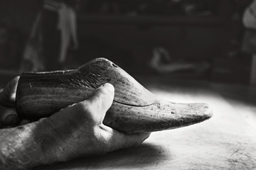 old hands hold old wood shoes model size